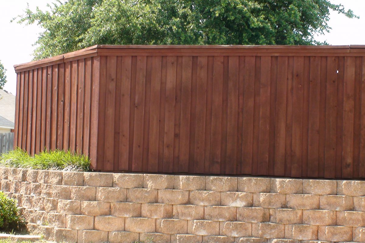 903 - Paver retaining wall with board on board fence